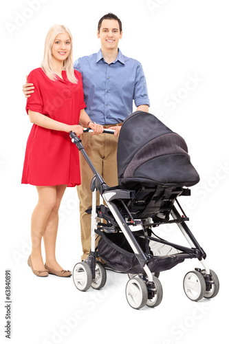 Young parents posing with a baby stroller