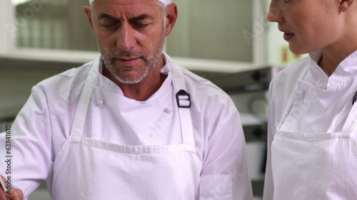 Chef showing colleague content of pot then smiling at camera