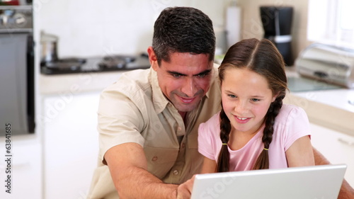 Father using the laptop with his daughter