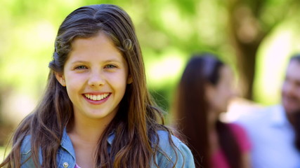 Little girl smiling at camera with family behind on park bench