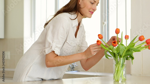 Woman smelling her vase of tulips and smiling at camera