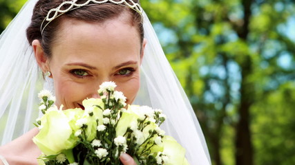 Pretty bride smiling at camera and smelling her bouquet