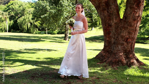Excited bride holding a bouquet in the park smiling at camera