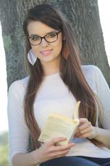 Jeune femme lisant un livre adossée à un arbre