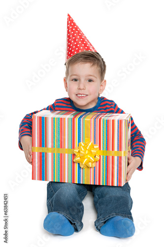 Little boy sits with a gift box