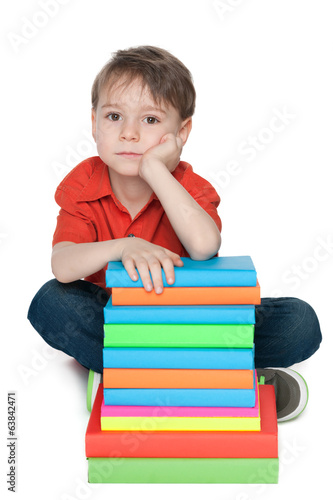Thoughtful little boy with books