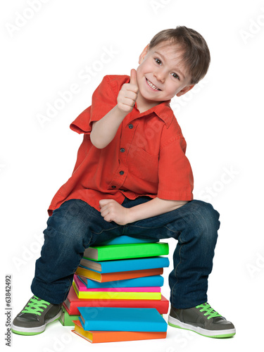 Sitting on the books cheerful boy