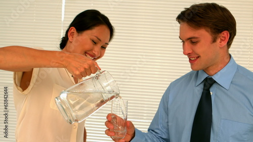 Businesswoman pouring her partner a glass of water