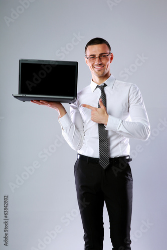 Smiling businessman standing with laptop and showing on it