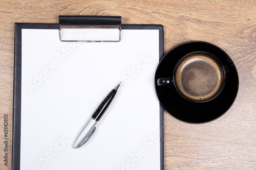 close up of blank clipboard, pen and cup of black coffee on wood