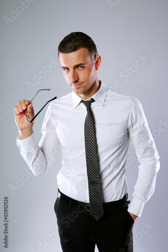 confident businessman holding his glasses