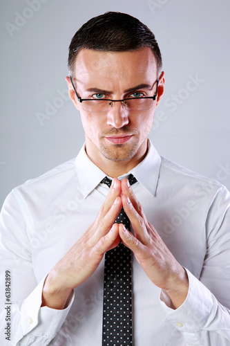 Confident businessman folding his hands together