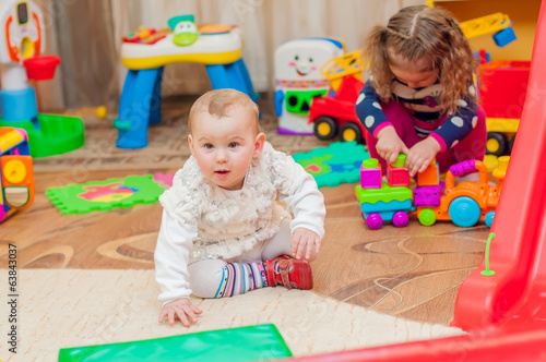 Little girl playing with toys in the playroom