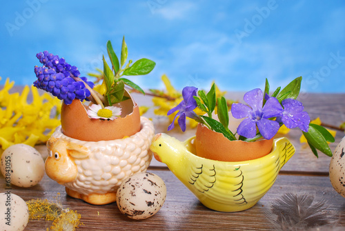 egg shells with spring flowers in ceramic stands for easter
