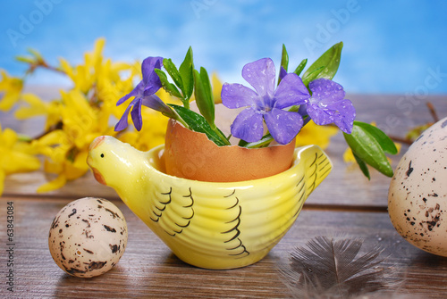 egg shell with flowers in hen shape stand for easter