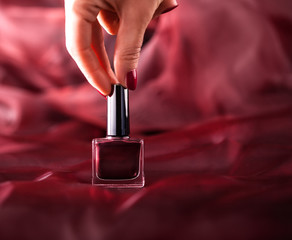 Red nail polish on silk drapery.