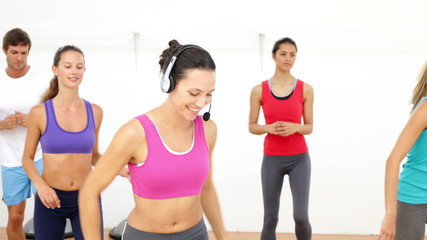 Aerobics class stepping together led by instructor
