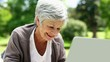 Happy senior woman relaxing in the park using her laptop