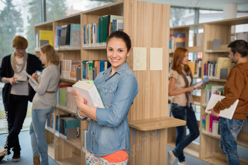 Student holding books in library