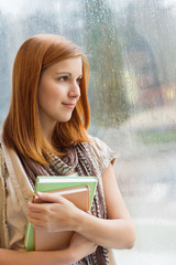 Thoughtful student with books by window