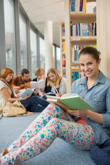 Student sitting in school library with friends