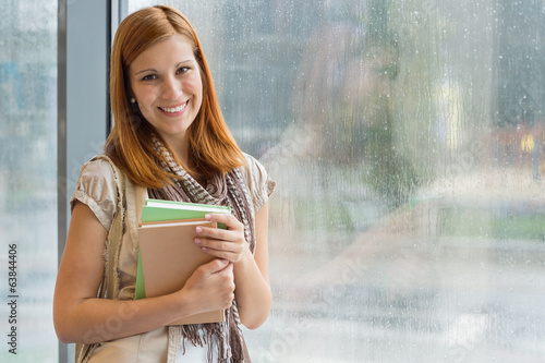 Student with books standing by window