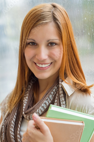 Student holding books in front of window