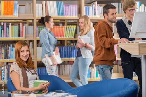 Smiling student in library with friends