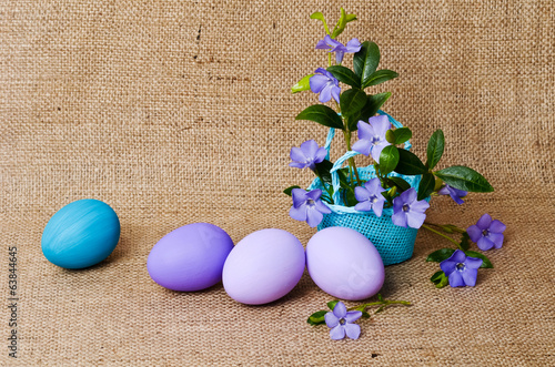 Beautiful periwinkles in a blue small basket with easter eggs