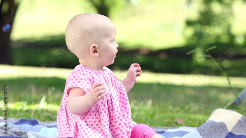 Baby girl playing with bubbles in the park