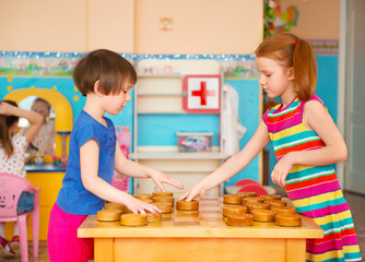 Two little girls playing in checkers at kindergarten
