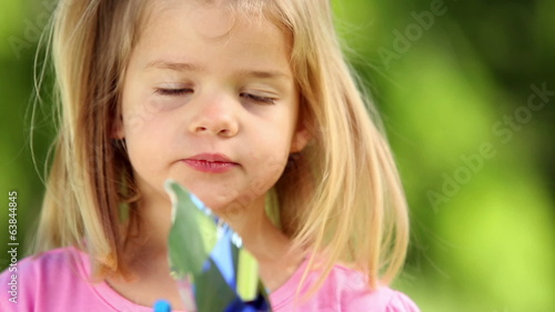 Little girl playing with pinwheel in the park