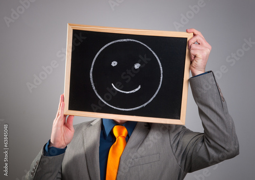 Businessman hiding his face with a white billboard with a smiley