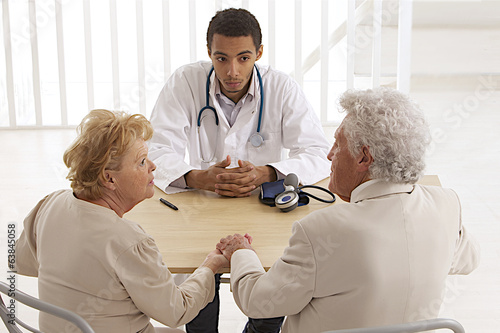 african-American doctor talking to senior couple