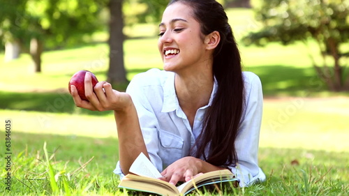 Pretty girl lying on the grass reading a book