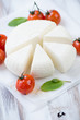 Sliced adygea cheese with cherry tomatoes and mint, close-up
