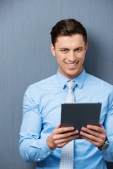 lächelnder mann liest am tablet-pc