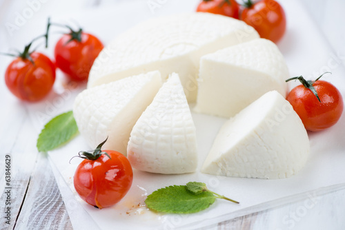 Close-up of adygea cheese, baked tomatoes and mint