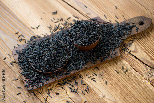 Chopping board with raw wild rice, horizontal shot