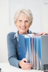 lächelnde ältere frau mit ordnern am schreibtisch
