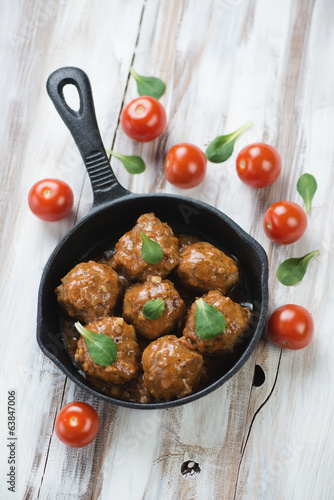 Meatballs with cherry tomatoes and corn salad leaves, above view