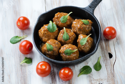 Frying pan with meatballs, cherry tomatoes and corn salad leaves