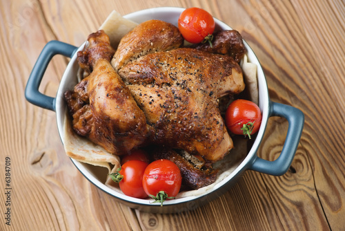 Whole baked spicy chicken with cherry tomatoes, high angle view