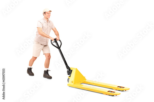 Male worker pushing a fork pallet truck