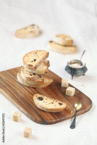 Cardamom Raisin Biscotti on a wooden cutting board.