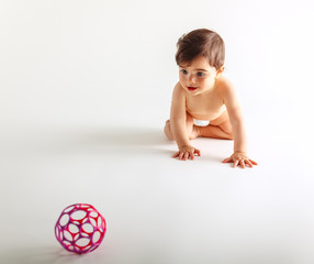 Cute baby girl in diapers crawling and play with ball.