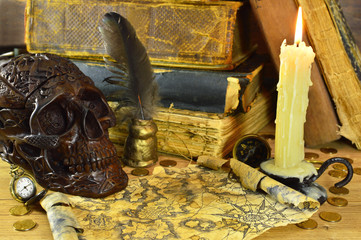 Skull with burning candle, map and books