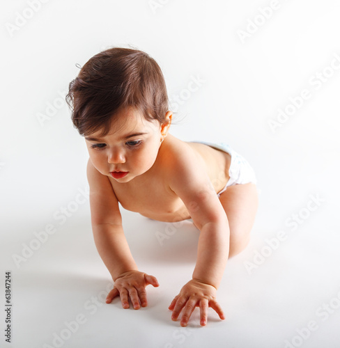Cute baby girl in diapers crawling.