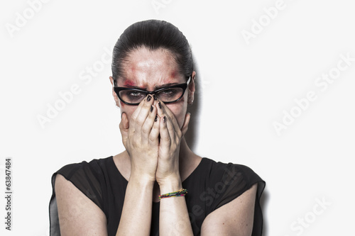 Beaten up girl crying and covering mouth with hands