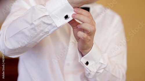 man wears white shirt and cufflinks